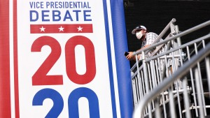 "A worker stands next to a sign that reads ""Vice Presidential Debate 2020"""