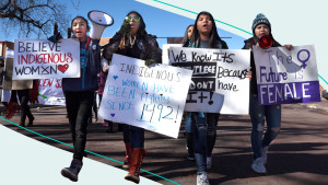 Native American participants in the Women's March walk with signs and bullhorns in Santa Fe, New Mexico.