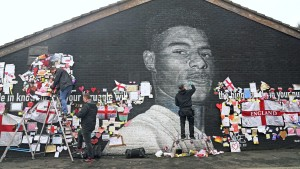 Street artist Akse P19 repairs the mural of Manchester United striker and England player Marcus Rashford