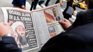 A man reading the newspaper about Osama bin Laden's capture and death. Got Him and Rot in Hell are some of the headlines.