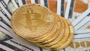 Bitcoin cryptocurrency commemorative coins seen on top of the US dollars.