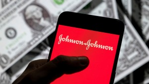 In this photo illustration, the American multinational medical devices and pharmaceutical company Johnson & Johnson logo seen on an Android mobile device screen with the currency of the United States dollar icon, $ icon symbol in the background.