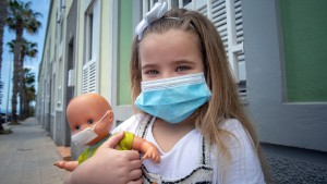 Girl and her doll pose wearing a face mask.