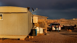 A Navajo woman carries wood to heat her rural mobile home during the coronavirus pandemic in Cameron, Arizona.