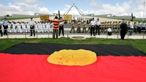 An Aborigonal protester sits outside Parliament House during the opening of the 42nd Parliament