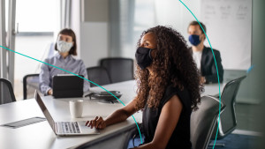 Team of business professionals wearing face mask sitting in office boardroom during a meeting.