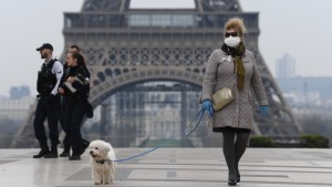 A woman wears protective gloves and a mask near the Eiffel Tower