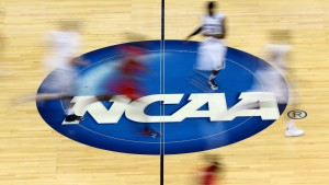 Mississippi Rebels and Xavier Musketeers players run by the logo at mid-court during the second round of the 2015 NCAA Men's Basketball Tournament at Jacksonville Veterans Memorial Arena on March 19, 2015 in Jacksonville, Florida.