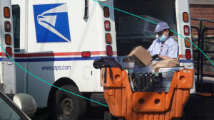 A postal worker loads a delivery truck