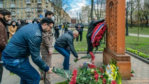 People leave flowers under a khachkar, a memorial stone stele of armenian culture, during the Armenian Genocide Remembrance Day in Kiev, Ukraine.