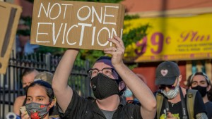 A participant holding a Not One Eviction sign at the protest