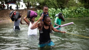 Haitian migrants cross the Rio Grande river at US-Mexico border to get food and water in Mexico on September 21, 2021.