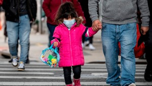 A girl, wearing a mask, walks down a street in the Corona neighborhood of Queens on April 14, 2020 in New York City.