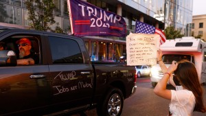 A BLM protester block Pickup trucks and cars full of flag-waving Donald Trump supporters