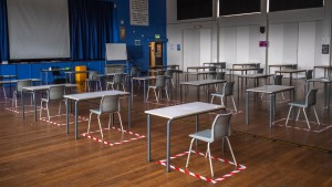 Socially distanced desks are set out for lesson in the hall at All Saints Catholic College in Dukinfield, England