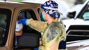 """Medical personnel conduct Covid-19 testing at a """"drive-through"""" site"""