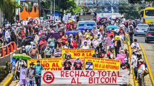 Demonstrators march while holding anti-bitcoin signs during the protest march in San Salvador.