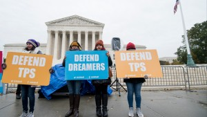 Protesters hold signs supporting dreamers and TPS outside of the U.S. Supreme Court