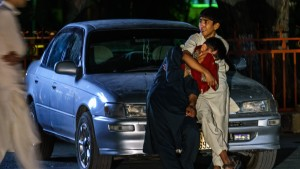 Two boys embrace each other as they weep in the parking lot at Wazir Akbar Khan hospital