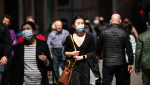 People wear face masks while walking in New York City.