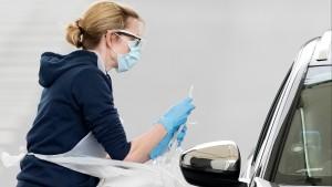 A nurse takes a swab at a Covid-19 Drive-Through testing station