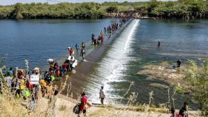 Migrants walk across the Rio Grande River in Del Rio, Texas in September 2021.