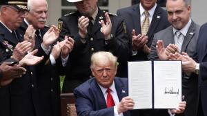 """President Trump holds up an executive order he signed on """"Safe Policing for Safe Communities"""" on June 16th, 2020."""