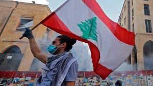 A Lebanese protester waves a national flag amid clashes with security forces