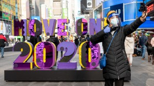 "Woman stands in front of sign that says ""Move On 2020"" in Times Square."
