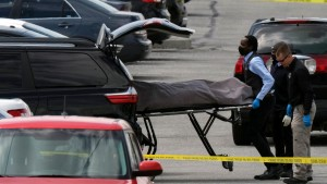 Officials load a body into a vehicle at the site of a mass shooting at a FedEx facility in Indianapolis, Indiana, on April 16, 2021.