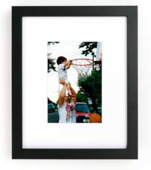 Framed photo of dad holding up son to dunk basketball
