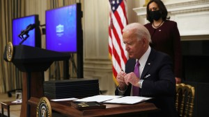 U.S. President Joe Biden signs executive orders as Vice President Kamala Harris looks on during an event at the State Dining Room of the White House January 21, 2021.