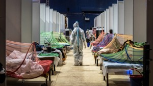 A medical worker in PPE observes patients who have been infected by Covid-19 inside a makeshift covid care facility in a sports stadium at the Commonwealth Games Village in New Delhi on May 02, 2021.