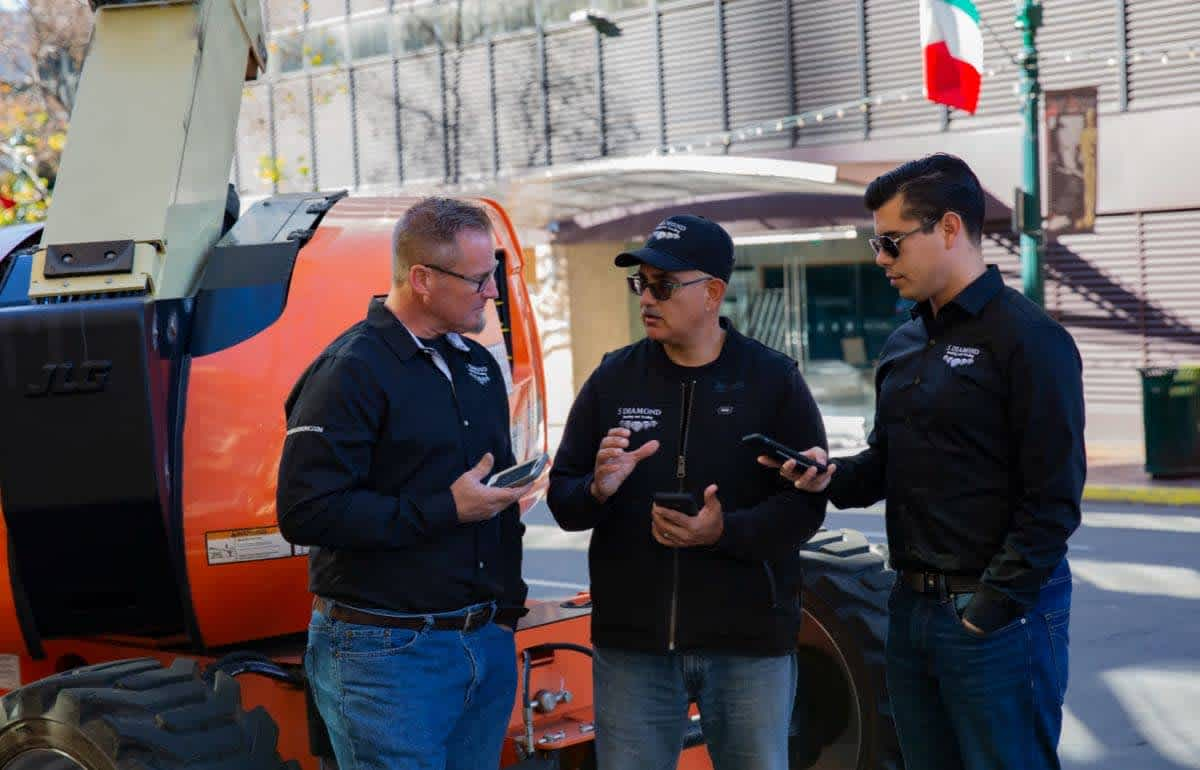 Three HVAC pros standing together with mobile phones in hand talking to each other about a job
