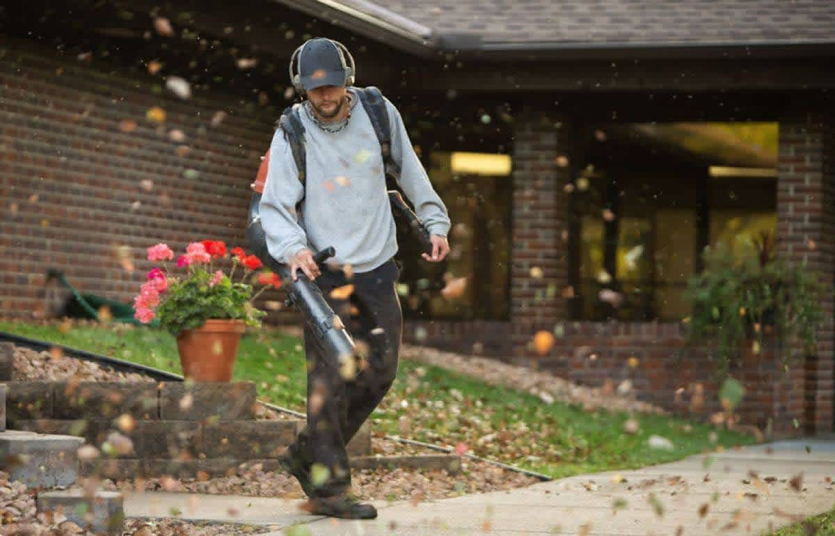 Lawn care pro blowing leaves from a sidewalk.