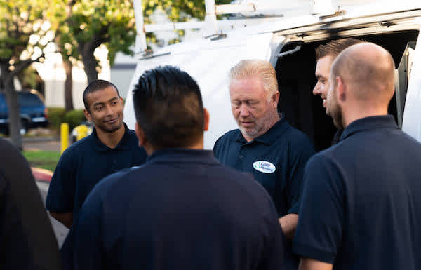 Group of Pros standing in a circle next to a work van talking and smiling