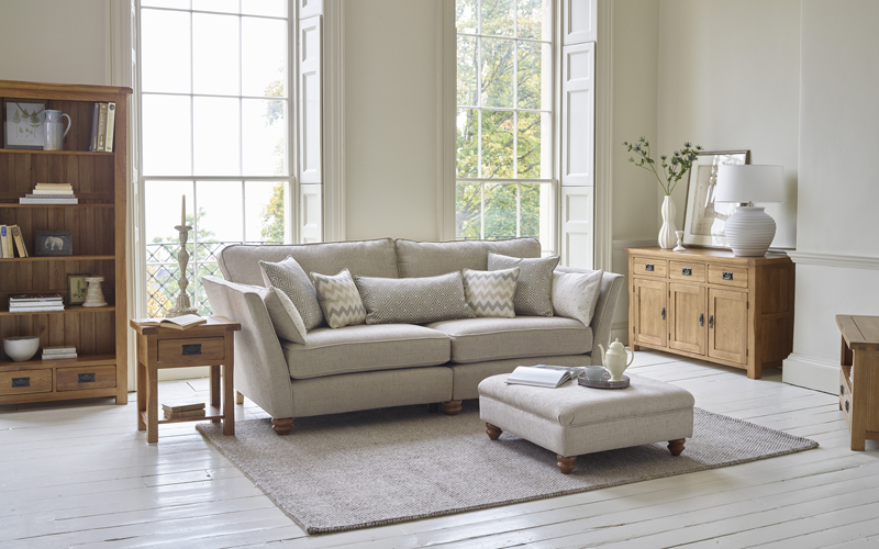 Traditional living room furniture with light grey sofa and footstool