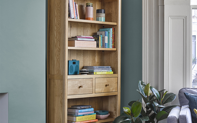 scandinavian style bookcase with colourful books and accessories