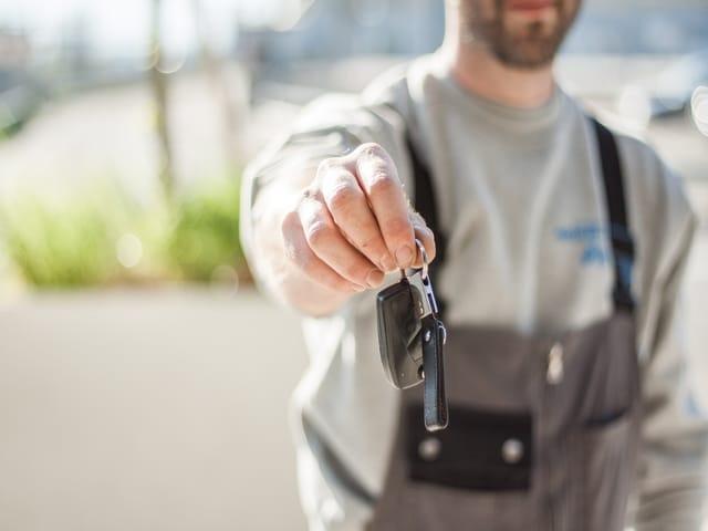 man holding car keys new zealand car rental phone