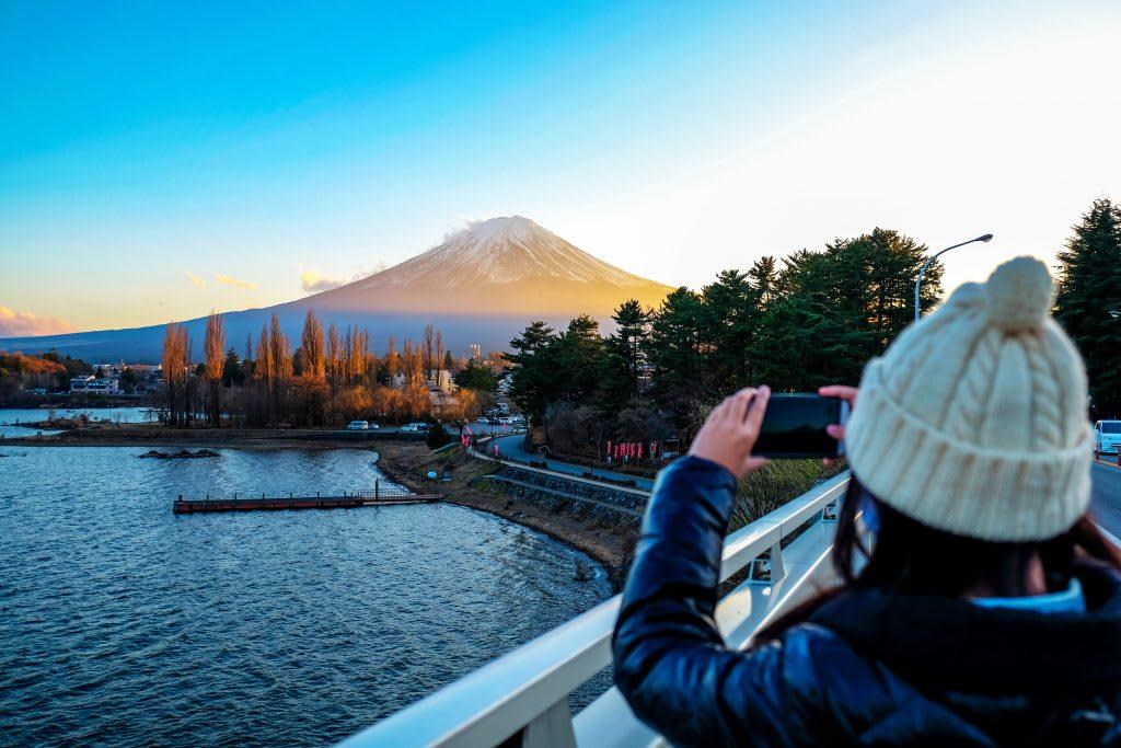 Woman taking photos of Fuji Mountain with smartphone