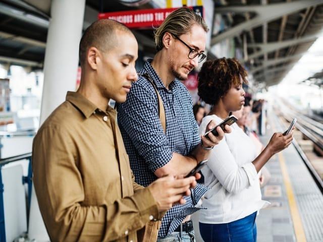 people standing train platform phones mobile distractd