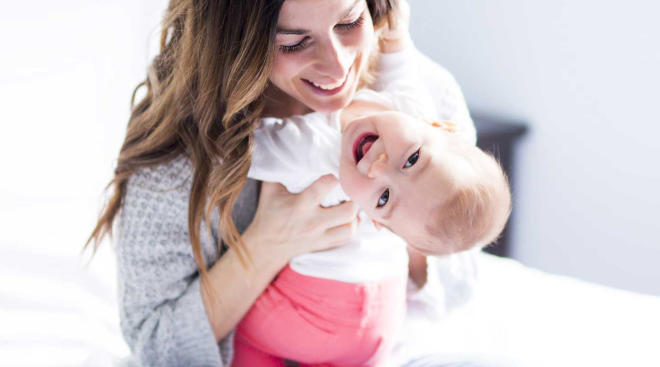 happy mom holding her baby, representing the alexis joy foundation
