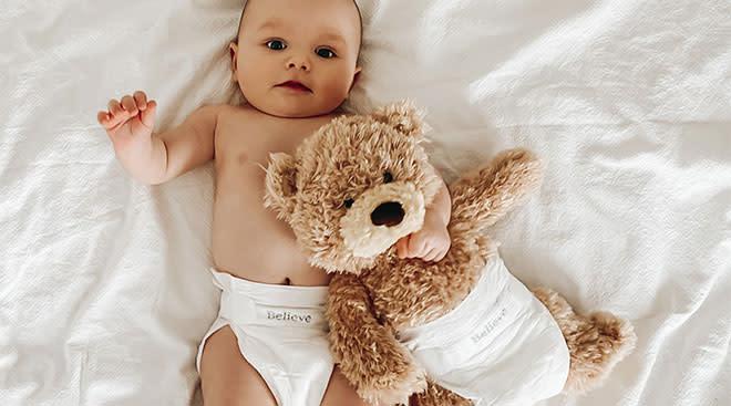 Baby wearing believe diaper brand.