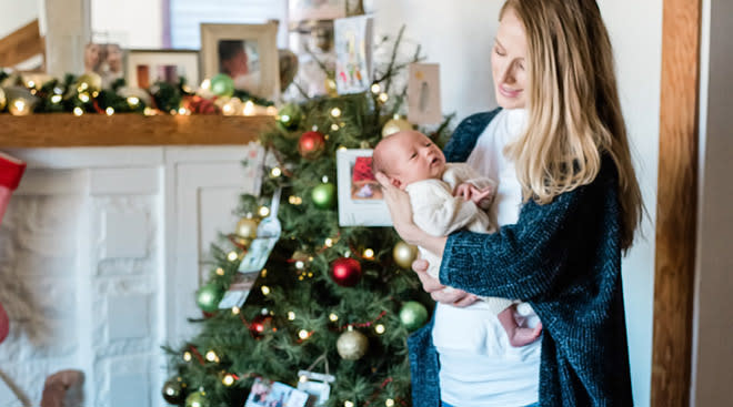 mom holding newborn baby by christmas tree filled with ornaments