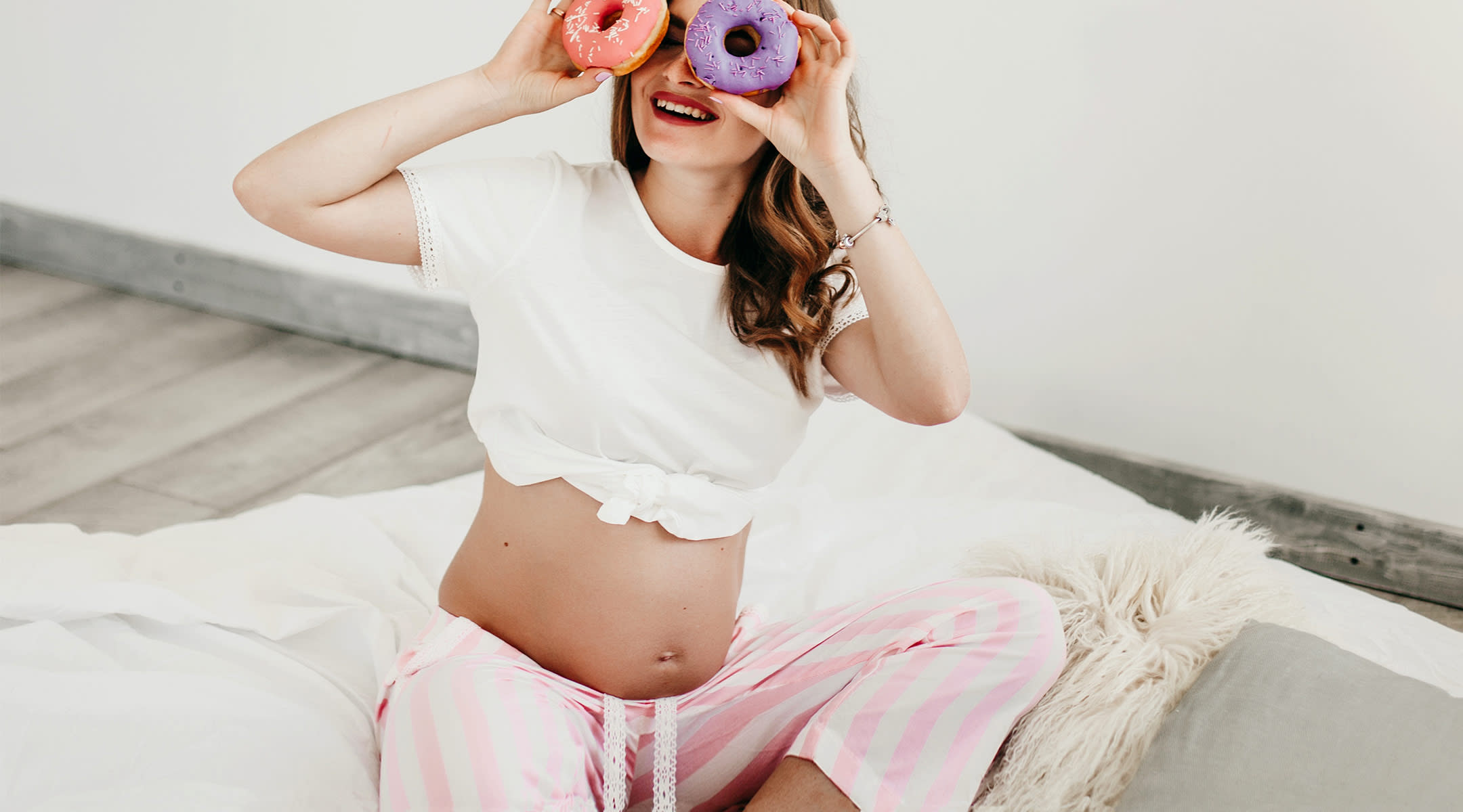 pregnant woman laughing and holding doughnuts up to her eyes