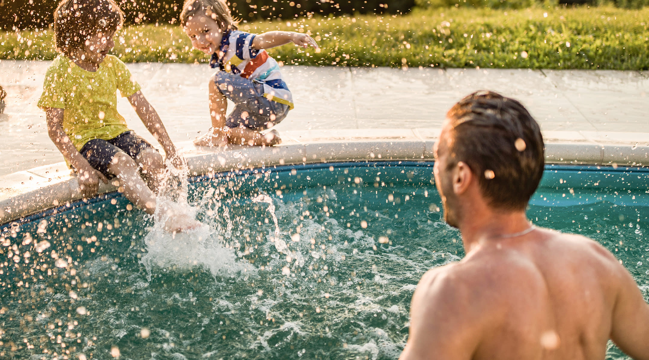 two little boys swimming in pool with dad nearby