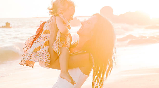 happy mom holding her daughter at the beach