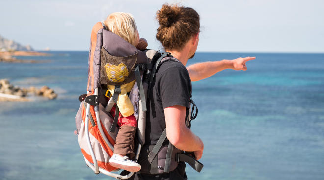 Travel tips Baby in pack with father while traveling by the sea