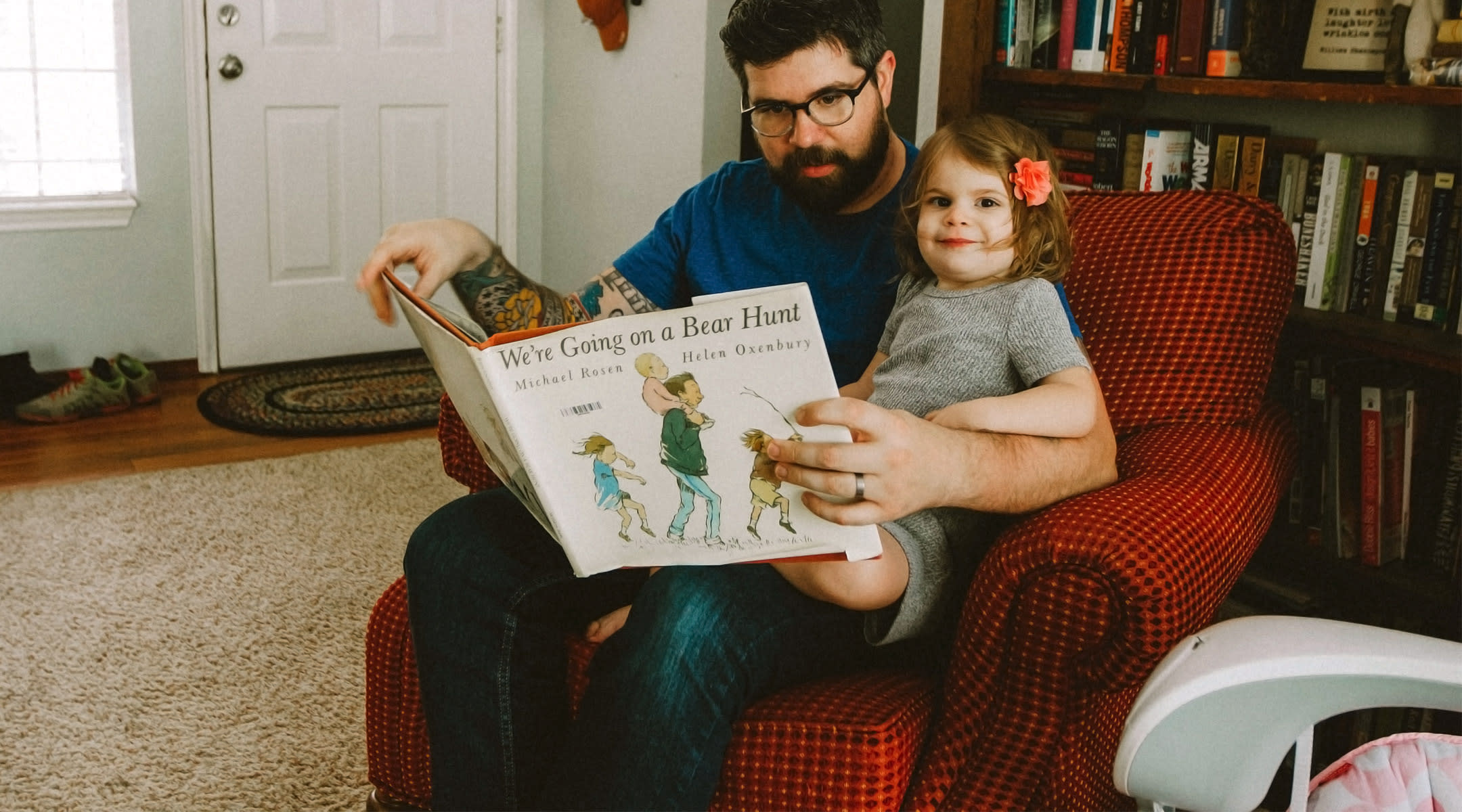 toddler sitting with her dad while reading a book