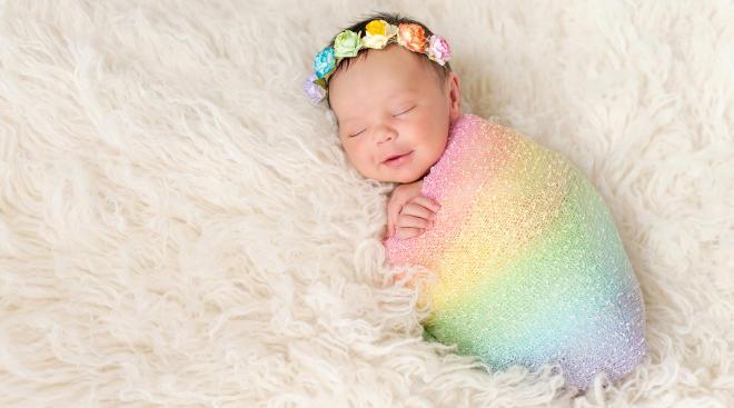 Rainbow baby wearing rainbow blanket